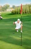 排队轻轻一击的高尔夫球运动员。 库存照片