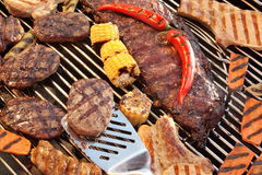 排骨、牛排、汉堡包小馅饼、玉米和胡椒在Gri 免版税库存图片