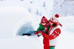 掠过和铲起雪的母亲和孩子汽车在风暴以后 父母和孩子与冬天刷子和刮板清洁家用汽车 库存图片