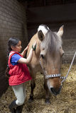 掠过她偏爱的马的小女孩 免版税库存照片