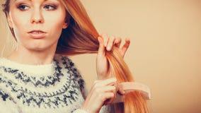 掠过她的有梳子的少年白肤金发的女孩头发 免版税库存照片