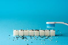 掠过的牙 牙刷从牙清洗土 糖立方体和芝麻籽讽喻 牙齿保护概念 口腔卫生 免版税库存图片