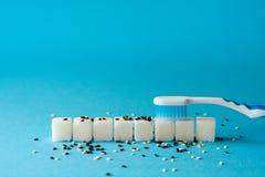 掠过的牙 牙刷从牙清洗土 糖立方体和芝麻籽讽喻 牙齿保护概念 口腔卫生 免版税库存照片