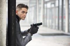 年轻探员或警察或者流氓拿着枪的一个城市布局的 库存图片