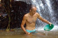 探油矿者摇摄金子在有水闸箱子瀑布的一条河在背景中 免版税库存照片
