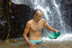 探油矿者摇摄金子在有水闸箱子瀑布的一条河我 免版税图库摄影