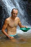 探油矿者摇摄金子在有水闸箱子瀑布的一条河我 库存图片