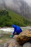 探油矿者摇摄金子在有水闸箱子的一条河在雨天 库存照片