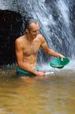 探油矿者摇摄金子在有水闸箱子的一条河有waterf的 图库摄影