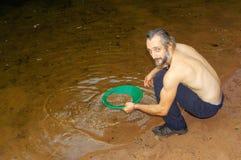 探油矿者摇摄金子在有水闸箱子的一条河 免版税库存照片