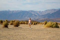 探索和步行在死亡谷沙漠下的美丽的女孩 图库摄影