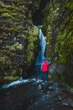 探索瀑布的徒步旅行者在冰岛 免版税库存照片