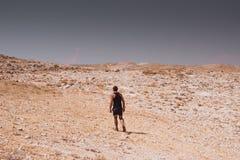 探索-偏僻人走在岩石沙漠自由和冒险生活方式和体育概念 库存图片