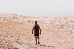 探索-偏僻人走在岩石沙漠自由和冒险生活方式和体育概念 免版税库存图片