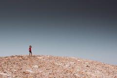 探索-走在岩石沙漠自由和冒险生活方式和体育概念的孤独的男孩 库存图片