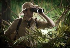 探险家在有双筒望远镜的密林 免版税库存照片