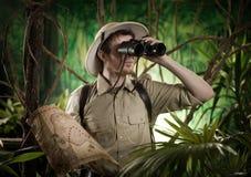 探险家在有双筒望远镜的密林 免版税库存图片