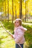 探险家女孩用棍子在白杨树黄色秋天森林里 免版税库存照片
