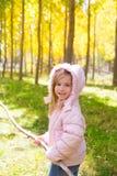 探险家女孩用棍子在白杨树黄色秋天森林里 库存照片