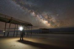 探索一个损坏的码头的人在晚上 免版税库存照片