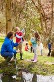 探索池塘的成人和孩子在活动中心 免版税图库摄影
