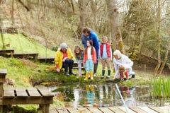 探索池塘的成人和孩子在活动中心 图库摄影