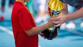 接受一奖杯的运动服的孩子 赢取体育学校竞争的年轻运动员 有金黄奖牌的男孩 免版税库存照片