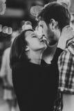 接受亲吻的一对愉快的夫妇的黑白照片在轻的诗歌选的晚上 免版税库存图片