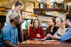 接受从客户的黑围裙的微笑的年轻女服务员命令咖啡馆的 休闲、人们、食物咖啡馆和假日 库存照片