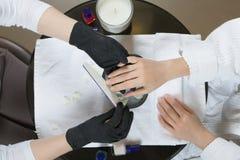 接受修指甲和钉子关心做法关闭的妇女手  免版税库存图片