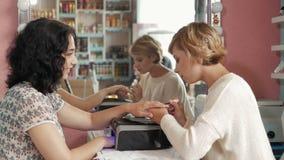 接受修指甲的钉子沙龙的妇女由有文件的美容师 获得 对顾客的钉子 蠢材 免版税图库摄影