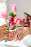 接受修指甲的钉子沙龙的妇女 免版税库存图片