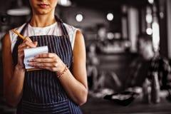 接受命令的女服务员在餐馆 免版税库存图片