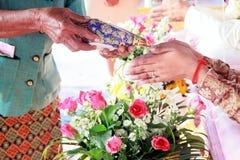 接受圣水的新娘的手从在泰国文化婚礼的长辈 库存照片