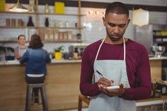 接受在咖啡馆的所有者命令 免版税库存图片