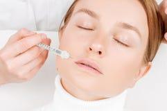 接受在嘴唇的美女补白射入 防皱治疗和整形 免版税库存照片
