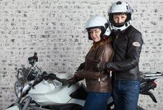 接受在摩托车成套装备的年轻人夫妇一起站立在车库的摩托车附近 免版税库存图片