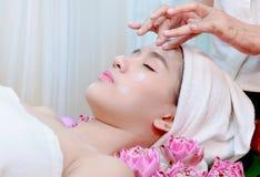 接受在温泉美容院的亚裔妇女黏土面部面具 库存图片