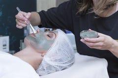 接受在温泉美容院的年轻美丽的女孩医疗面部面具-户内 免版税库存图片