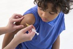 接受在胳膊的男孩疫苗 库存照片