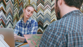 接受在画框的年轻女性卖主命令从男性顾客在柜台在商店 免版税库存照片