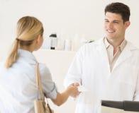 接受处方纸的药剂师从顾客在商店 免版税库存图片