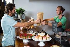 接受小包的微笑的顾客从职员在柜台 库存图片