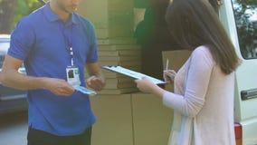接受小包的邮递员从女性和给的收据,国际运输 股票录像