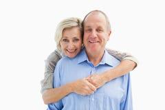 接受微笑对照相机的愉快的成熟夫妇 图库摄影