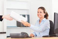 接受微笑的女实业家纸堆 免版税图库摄影