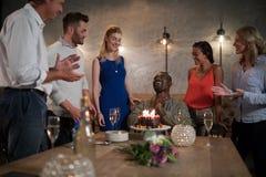 接受惊奇生日蛋糕的人从她的朋友 免版税库存照片