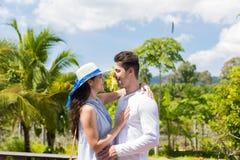 接受户外在大阳台的男人和妇女愉快的微笑的年轻夫妇在热带森林夏天风景  免版税图库摄影