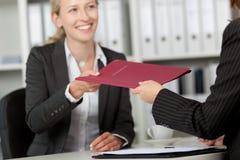 接受文件的女实业家从工友在书桌 免版税库存照片