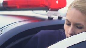 接受无线电呼叫的负责任的警察夫人,进入汽车准备好帮助 股票录像